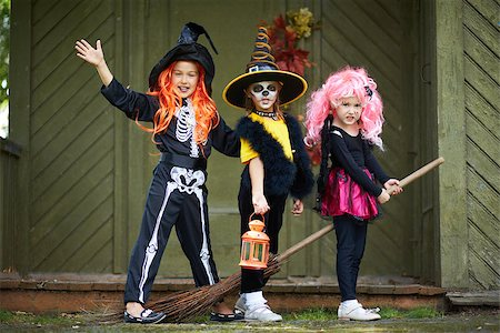 Portrait of three Halloween girls with broom looking at camera outside Stock Photo - Budget Royalty-Free & Subscription, Code: 400-07096174
