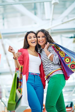 pressmaster (artist) - Joyful girls with paperbags looking at camera in trade center Stock Photo - Budget Royalty-Free & Subscription, Code: 400-07103805