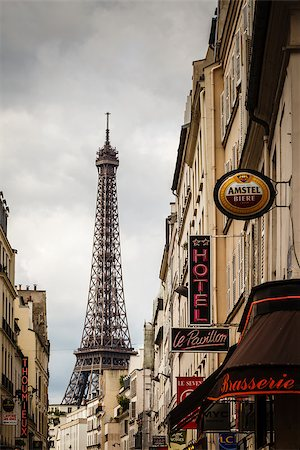 PARIS - JUNE 29: Parisian Street against Eiffel Tower on 29 June 2013 in Paris, France. The tower is the tallest structure in Paris and the most-visited paid monument in the world. Stock Photo - Budget Royalty-Free & Subscription, Code: 400-07115017