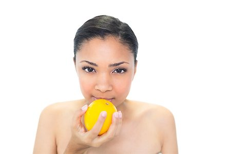 Calm young dark haired model smelling an orange on white background Stock Photo - Budget Royalty-Free & Subscription, Code: 400-07127108