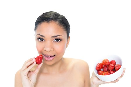 Relaxed young dark haired model eating strawberries on white background Stock Photo - Budget Royalty-Free & Subscription, Code: 400-07127114