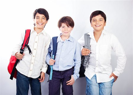 Three cheerful teenagers isolated on white background, back to school, best friends classmates, preteens standing and smiling  with backpacks and textbooks, knowledge and education concept Stock Photo - Budget Royalty-Free & Subscription, Code: 400-07123462