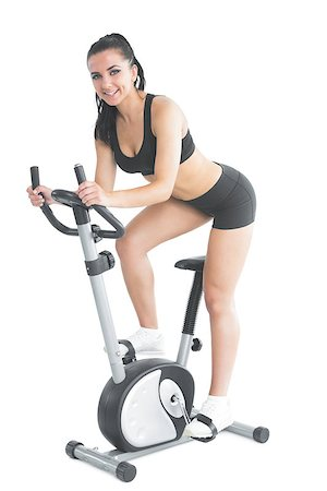 Beautiful young woman training on an exercise bike smiling at camera Stock Photo - Budget Royalty-Free & Subscription, Code: 400-07141550