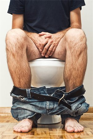 Man sitting on toilet with his pants down. Stock Photo - Budget Royalty-Free & Subscription, Code: 400-07169176