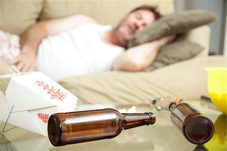 drunk passed out - Man passed out on his couch in his underwear.  A full ashtray, empty beer bottles and empty Chinese take out container scattered on his coffee table. Stock Photo - Budget Royalty-Free & Subscription, Code: 400-07179995
