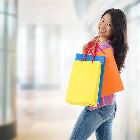 Happy Asian shopping woman smiling holding many shopping bags at the mall. Casual Asian shopper girl standing in department store. Beautiful mixed race Southeast Asian woman model. Stock Photo - Budget Royalty-Free & Subscription, Code: 400-07170003