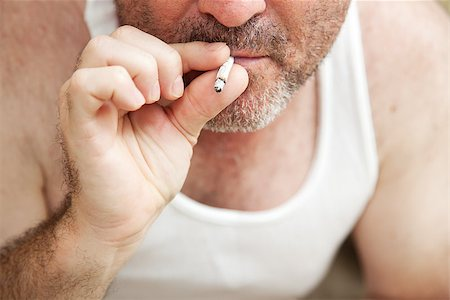 Closeup view of a man smoking a marijuana joint.  **Dramatization - no illegal narcotics were used in the making of this photograph** Stock Photo - Budget Royalty-Free & Subscription, Code: 400-07180005