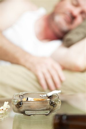 Ashtray with a joint of marijuana burning in the foreground, with a man asleep in the background.  Shallow depth of field.  **Dramatization - no illegal drugs were used in the making of this photograph** Stock Photo - Budget Royalty-Free & Subscription, Code: 400-07180002