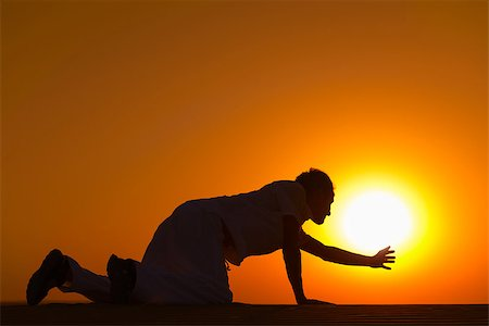Tired and weaken man on all fours reached his hand to gold sunset sun disk to pray for help Stock Photo - Budget Royalty-Free & Subscription, Code: 400-07210143