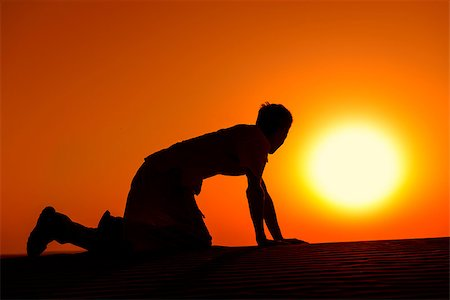 Tired and weaken man on all fours with gold sunset sun disk on background Stock Photo - Budget Royalty-Free & Subscription, Code: 400-07254498