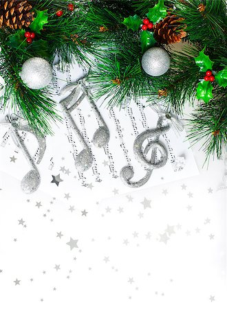 Photo of Christmas tree border, silver treble clef, festive melody on the notes page, musical sound, traditional Christmastime song, green pine tree branch decorated with cones, red berry and baubles Stock Photo - Budget Royalty-Free & Subscription, Code: 400-07260855