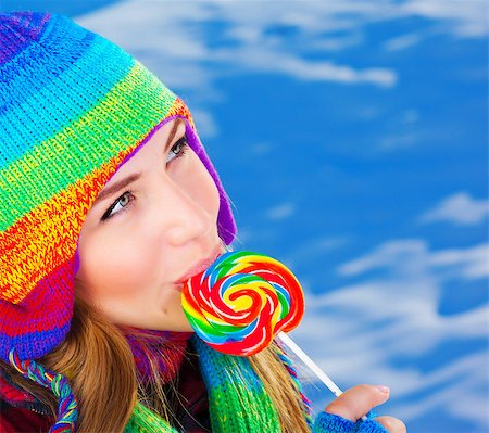 Photo of pretty girl eating sugar candy outdoor in wintertime, closeup portrait of beautiful female wearing warm colorful hat and licking lollipop, christmas sweets, sweet food, winter vacation Stock Photo - Budget Royalty-Free & Subscription, Code: 400-07263920