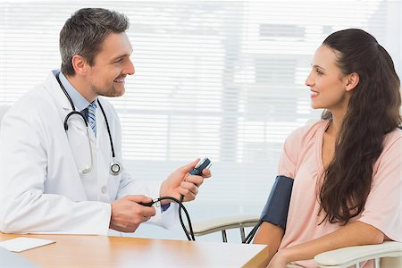 Male doctor checking blood pressure of a young woman at the medical office Stock Photo - Budget Royalty-Free & Subscription, Code: 400-07274823