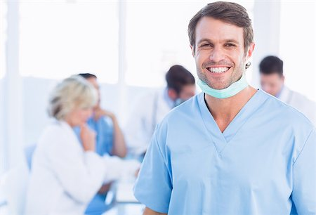 Portrait of a smiling male surgeon with colleagues in meeting at a medical office Stock Photo - Budget Royalty-Free & Subscription, Code: 400-07276019