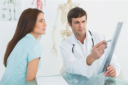 Side view of a male doctor explaining x-ray to female patient in the medical office Stock Photo - Budget Royalty-Free & Subscription, Code: 400-07270843