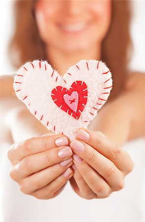 Picture of a small white heart in hands, female holds handmade sewn soft toy, macro, shallow dof, woman with Valentine gift, happy girl smiling, conceptual image of health care or love Stock Photo - Budget Royalty-Free & Subscription, Code: 400-07272531