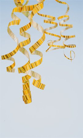 party celebration paper confetti - Arrangement of Five Striped Yellow Curly Streamers Hanging Down isolated on Blue background Stock Photo - Budget Royalty-Free & Subscription, Code: 400-07299045