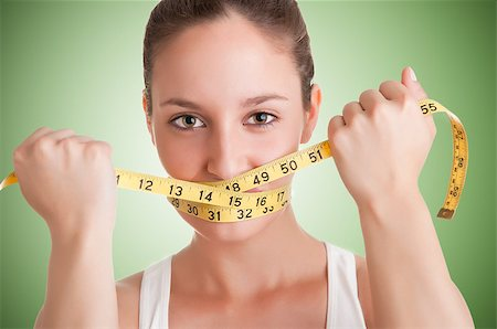 Woman with a yellow measuring tape around her mouth, in a green background Stock Photo - Budget Royalty-Free & Subscription, Code: 400-07290754