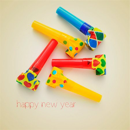 picture of some party horns of different colors and the sentence happy new year on a beige background, with a retro effect Stock Photo - Budget Royalty-Free & Subscription, Code: 400-07301972