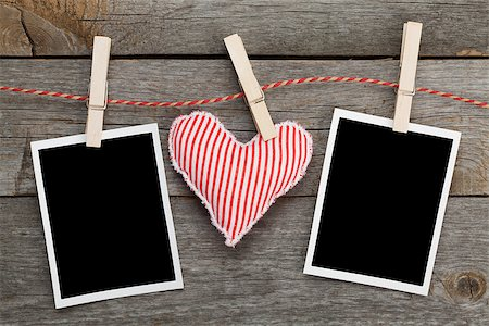 Two blank instant photos and red heart hanging. On wooden background Stock Photo - Budget Royalty-Free & Subscription, Code: 400-07316769