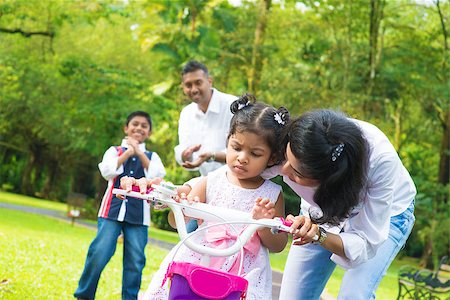 Indian family outdoor activity. Asian mother teaching little girl to ride a bike at the park in the morning. Stock Photo - Budget Royalty-Free & Subscription, Code: 400-07318235