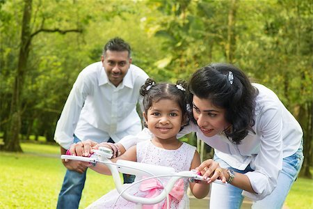 Indian family outdoor activity. Asian parent teaching child to ride a bike at the park in the morning. Stock Photo - Budget Royalty-Free & Subscription, Code: 400-07318236