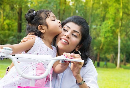 Indian family outdoor activity. Asian Mother teaching daughter cycling at the park in the morning. Child kissing parent. Stock Photo - Budget Royalty-Free & Subscription, Code: 400-07318237