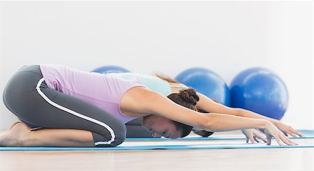 Side view of two sporty young women in meditation pose at fitness studio Stock Photo - Budget Royalty-Free & Subscription, Code: 400-07334776