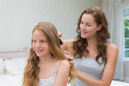 Beautiful young woman brushing little girl's hair in the bedroom at home Stock Photo - Budget Royalty-Free & Subscription, Code: 400-07339535