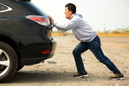 Man pushing a broken car down the rock road Stock Photo - Budget Royalty-Free & Subscription, Code: 400-07409060