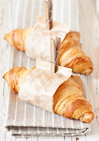 Fresh croissants wrapped in paper with clothespins on an old white board. Stock Photo - Budget Royalty-Free & Subscription, Code: 400-07414872