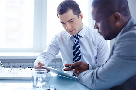 pressmaster (artist) - Image of two young businessmen using touchpad at meeting Stock Photo - Budget Royalty-Free & Subscription, Code: 400-07417775