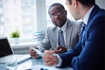 pressmaster (artist) - Image of two young businessmen interacting at meeting in office Stock Photo - Budget Royalty-Free & Subscription, Code: 400-07417779
