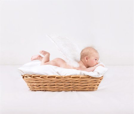 Baby with feather wings lying down in wicker basket isolated on white background, side view, sweet naked little angel, innocence concept Stock Photo - Budget Royalty-Free & Subscription, Code: 400-07428801