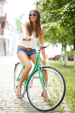 pressmaster (artist) - Portrait of a pretty woman on bicycle in the park Stock Photo - Budget Royalty-Free & Subscription, Code: 400-07421614