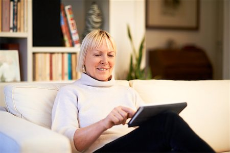 diego_cervo (artist) - portrait of beautiful old woman using tablet pc and smiling, sitting on sofa at home Stock Photo - Budget Royalty-Free & Subscription, Code: 400-07445657