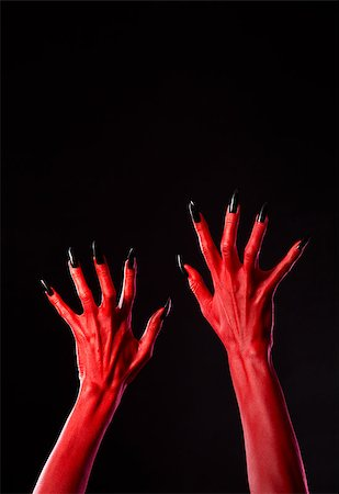 Red devil hands with black nails, Halloween theme, studio shot on black background Stock Photo - Budget Royalty-Free & Subscription, Code: 400-07465482