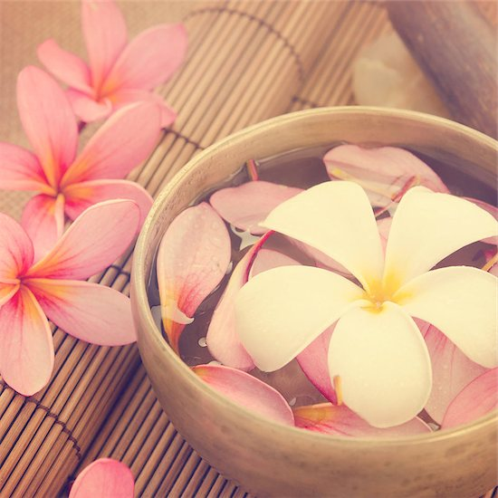 Spa setting, low light with ambient in vintage revival tone. Frangipani, hot and cold stone on bamboo mat. Stock Photo - Royalty-Free, Artist: szefei, Image code: 400-07470843