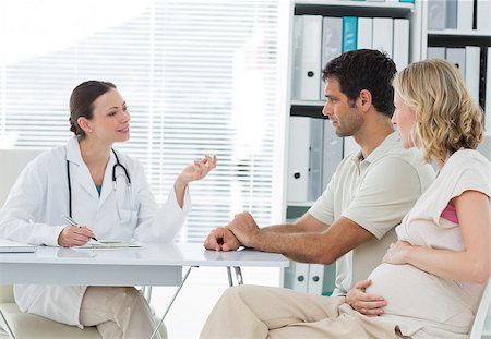 Female gynaecologist discussing with expectant couple in clinic Stock Photo - Budget Royalty-Free & Subscription, Code: 400-07473279