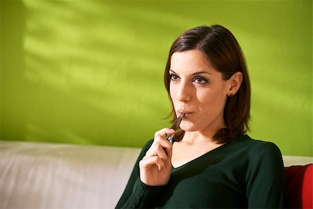 diego_cervo (artist) - young female smoker smoking e-cigarette at home, sitting on sofa and relaxing Stock Photo - Budget Royalty-Free & Subscription, Code: 400-07549590