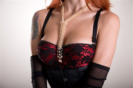 Busty redhead woman in vintage red bra, sheer gloves and pearl necklace Stock Photo - Budget Royalty-Free & Subscription, Code: 400-07549730