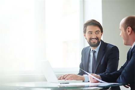 pressmaster (artist) - Image of handsome businessman typing and communicating with to his colleague at meeting Stock Photo - Budget Royalty-Free & Subscription, Code: 400-07552132