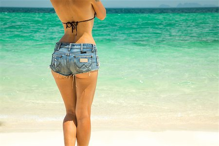Young beautiful woman in denim shorts sunbathing on the beach Stock Photo - Budget Royalty-Free & Subscription, Code: 400-07553490