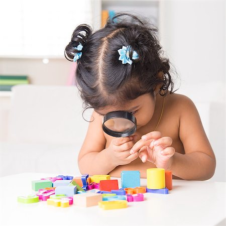 A little Indian girl zoom into toys through a magnifying glass, living lifestyle at home. Stock Photo - Budget Royalty-Free & Subscription, Code: 400-07553666