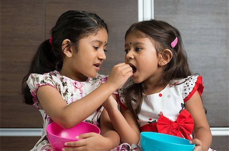 Indian girls sharing food, murukku with each other. Asian sibling or children living lifestyle at home. Stock Photo - Budget Royalty-Free & Subscription, Code: 400-07574718
