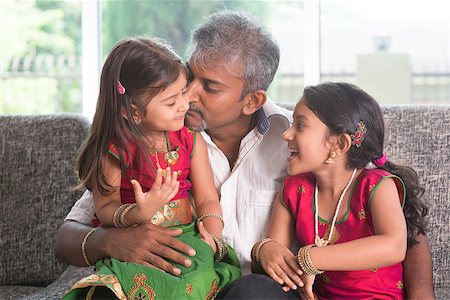 Happy Indian family at home. Asian father kissing her daughter, sitting on sofa. Parent and children indoor lifestyle. Stock Photo - Budget Royalty-Free & Subscription, Code: 400-07574725