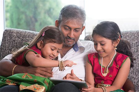 Indian family at home. Asian father and children using digital tablet computer, sitting on sofa, home schooling concept. Stock Photo - Budget Royalty-Free & Subscription, Code: 400-07574726