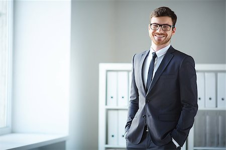 pressmaster (artist) - Handsome businessman in suit and eyeglasses looking at camera in office Stock Photo - Budget Royalty-Free & Subscription, Code: 400-07580314