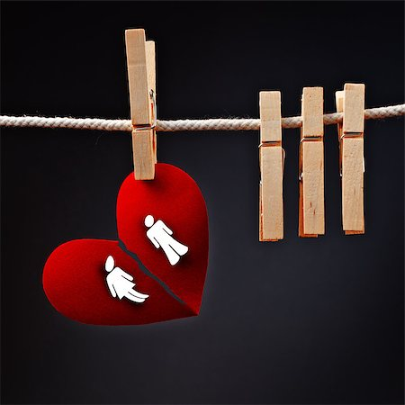 sad lovers break up - Heterosexual couple breaking apart, conceptual love image of paper heart ripped in two, hanging on rope with clothes pin. Stock Photo - Budget Royalty-Free & Subscription, Code: 400-07621788