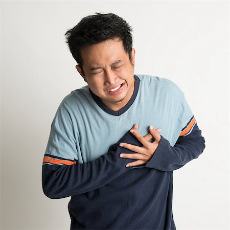 Asian male heartache, pressing on chest with painful expression, on plain background Stock Photo - Budget Royalty-Free & Subscription, Code: 400-07667608
